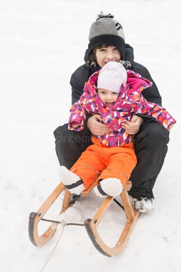 Kinder, die auf Winterschlitten spielen stockfotos