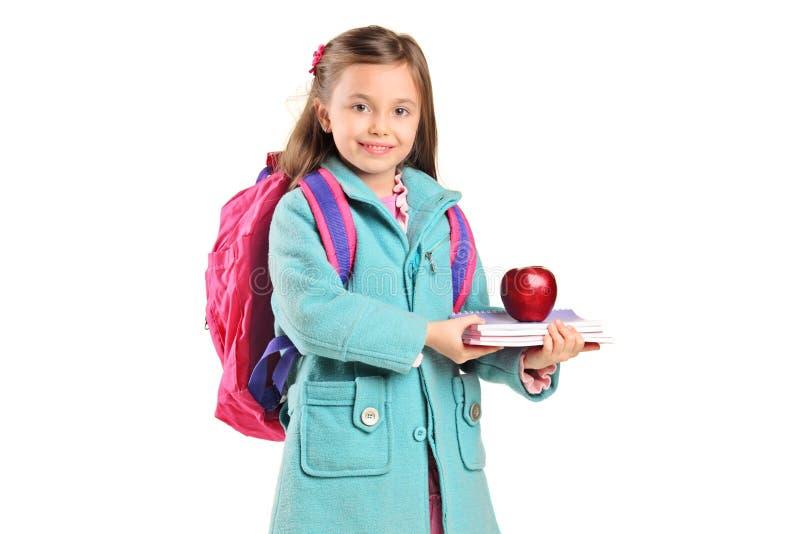 Kinder, die Bücher und Apfel anhalten stockbild