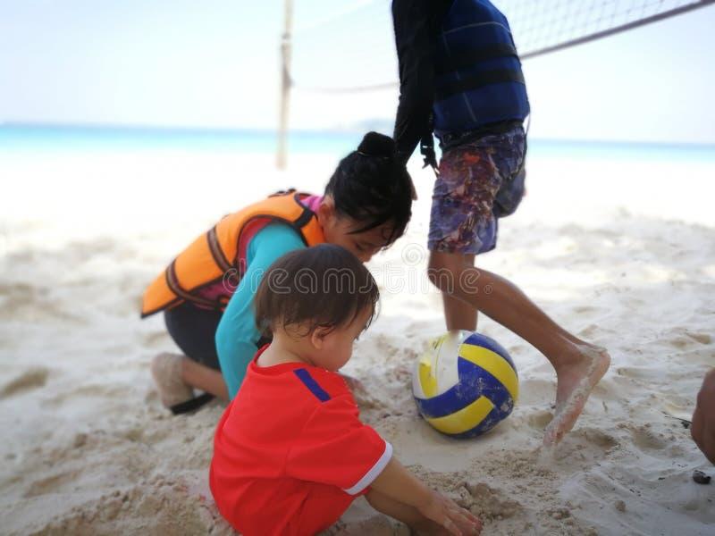 Kinder, die Ball durch den Strand in Pulau Redang spielen lizenzfreies stockfoto