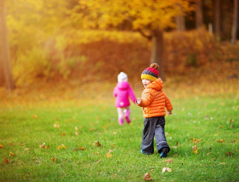 Kinder, die Bl?tter im sch?nen Herbsttag werfen stockbild