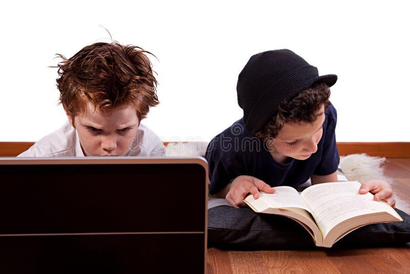 Kinder, die Computer spielen und ein Buch lesen lizenzfreie stockbilder