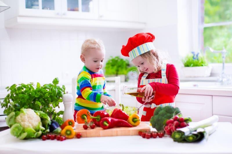 Kinder, die das gesunde vegetarische Mittagessen kochen stockbild