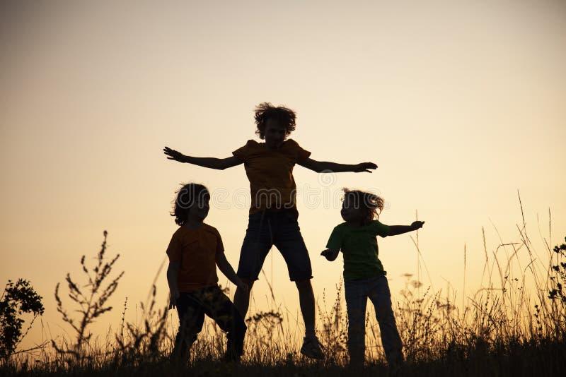 Kinder, die das Springen auf die Sommersonnenuntergangwiese silhouettiert spielen lizenzfreie stockfotos