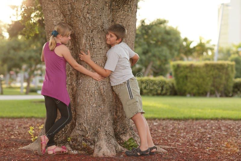 Kinder, die den Baum umarmen lizenzfreies stockfoto