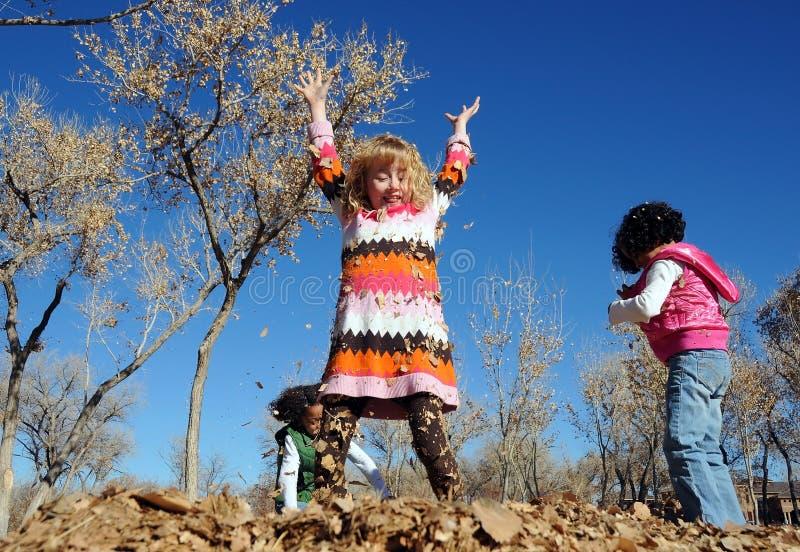 Kinder, die in den Blättern spielen lizenzfreies stockfoto
