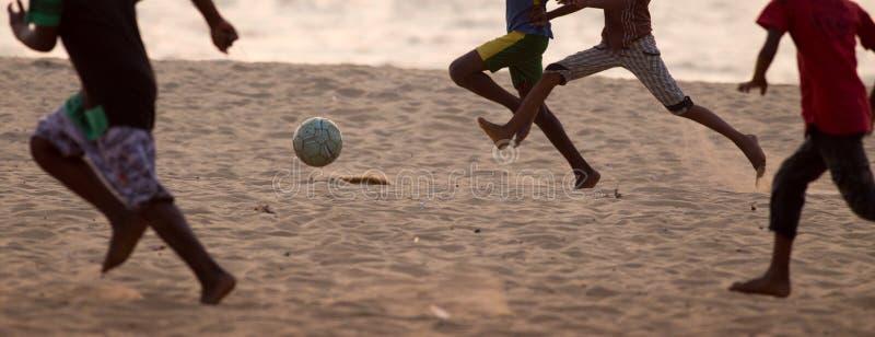Kinder, die den Fußball barfüßig auf Sand spielen lizenzfreie stockbilder