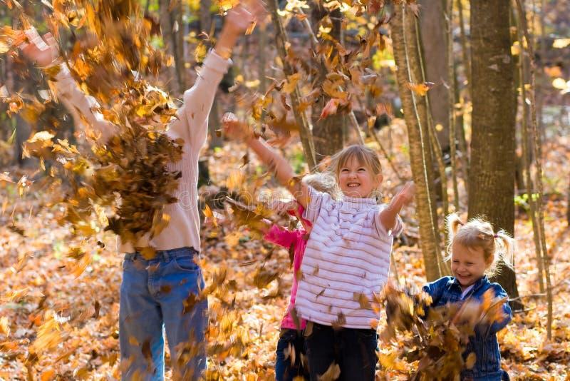 Kinder, die in den Herbstblättern spielen. lizenzfreie stockbilder