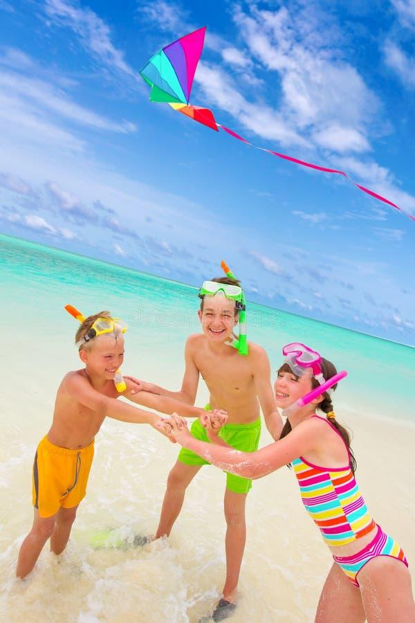 Kinder, die Drachen im Meer fliegen stockbilder