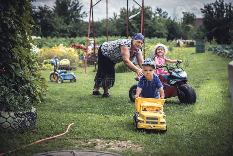 Kinder, die draußen mit aktiver älterer Großmutter in der Landschaft symbolisiert glückliche Kindheit spielen stockfotos