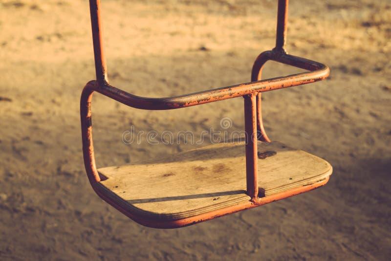 Kinder, die draußen rostiges Metall des Schwingens mit hölzernem Sitz hängen lizenzfreie stockbilder