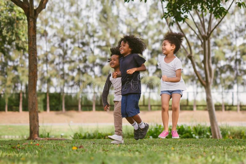 Kinder, die drau?en mit Freunden spielen kleine Kinderspiel am Naturpark lizenzfreie stockbilder