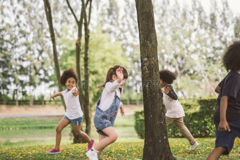 Kinder, die drau?en mit Freunden spielen kleine Kinderspiel am Naturpark lizenzfreies stockbild