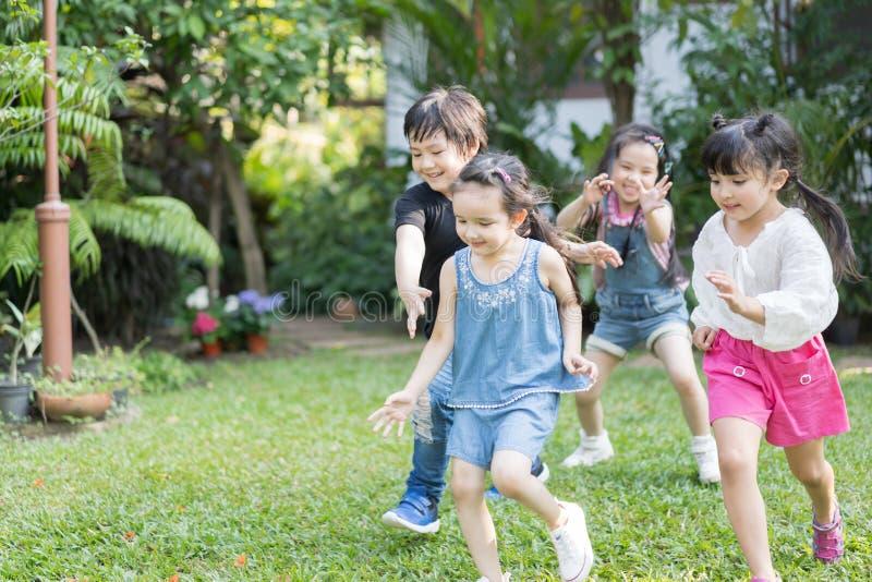 Kinder, die drau?en mit Freunden spielen kleine Kinderspiel am Naturpark lizenzfreie stockfotos