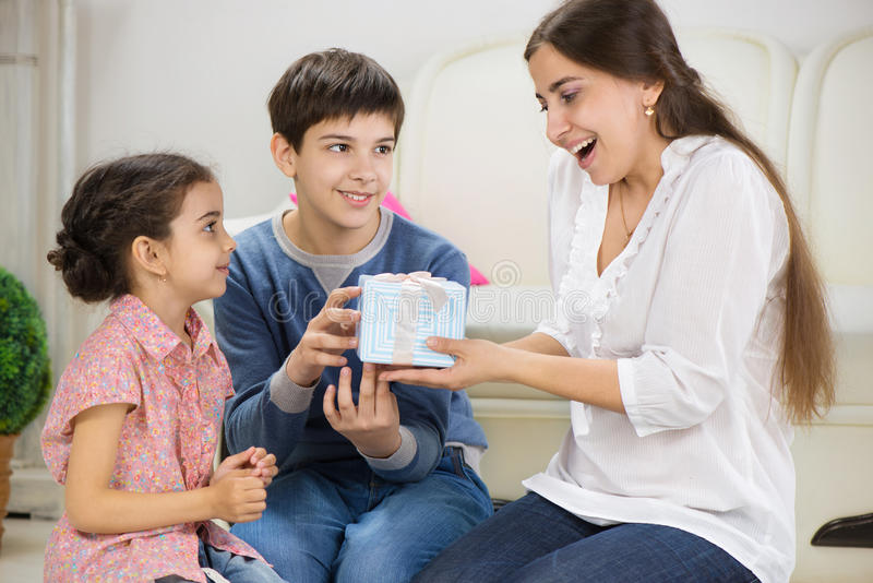 Kinder, die ein Geschenk Mutter darstellen lizenzfreie stockfotografie