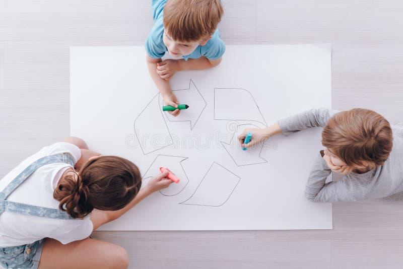 Kinder, die ein Plakat zeichnen stockfotos