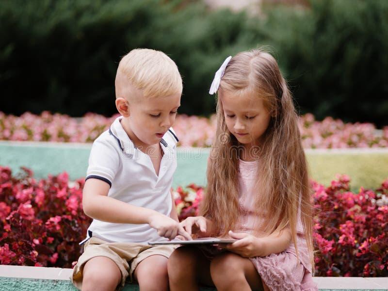 Kinder, die eine digitale Tablette lernen und im Park sitzen Ein Junge und ein Mädchen, die in einem Gerät auf einem natürlichen  stockfotos
