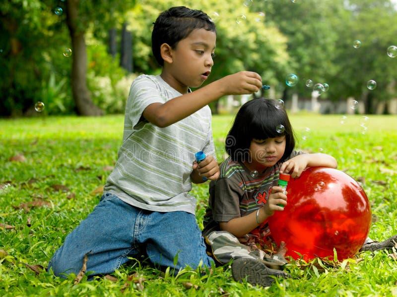 Kinder, die in einem Park spielen stockbild