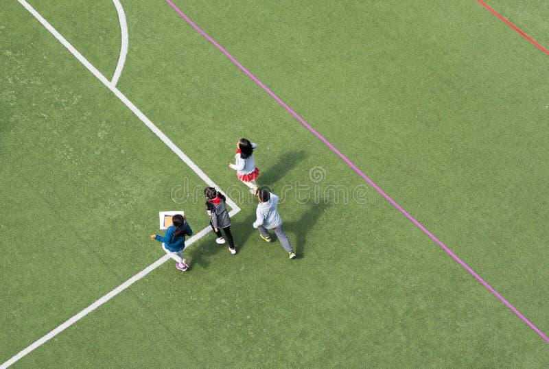 Kinder, die in einer hohen Winkelsicht des chinesischen Schulstadions spielen stockfotos