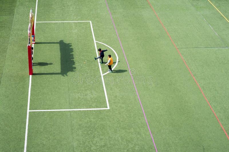 Kinder, die in einer hohen Winkelsicht des chinesischen Schulstadions spielen lizenzfreie stockfotografie
