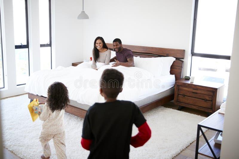 Kinder, die in Eltern Schlafzimmer mit Geschenk und Karte im Bett laufen lassen, um Mutter-Tag oder Geburtstag zu feiern lizenzfreie stockfotos