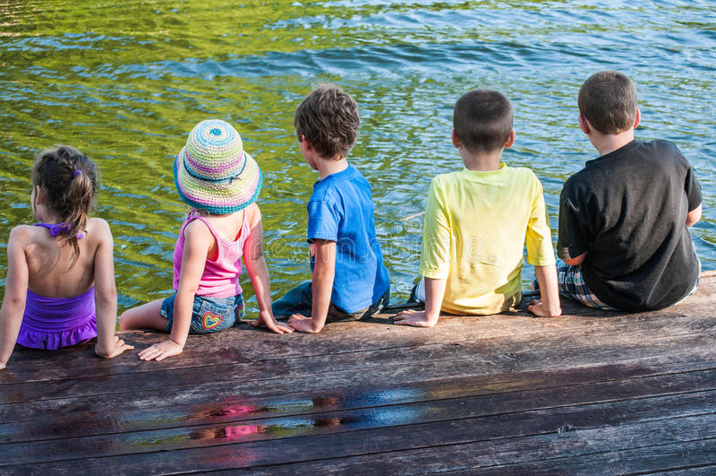 Kinder, die am Ende eines Docks sitzen stockfotografie