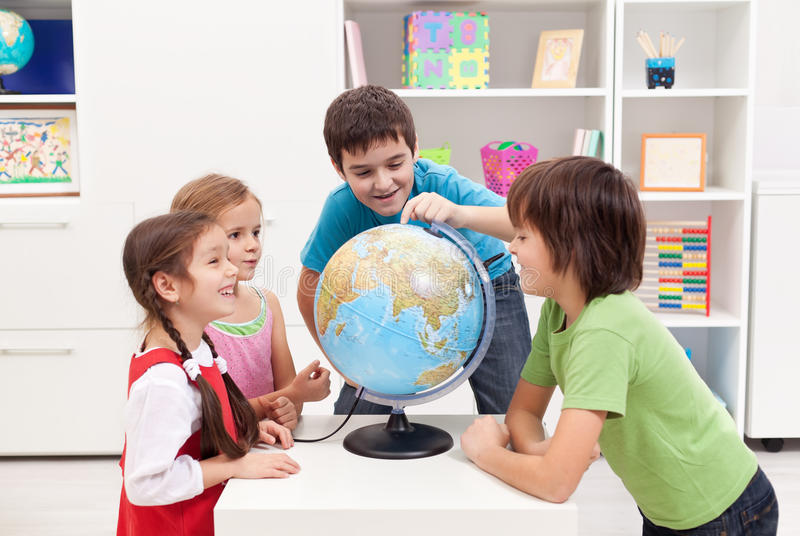 Kinder, die Erdkugel betrachten lizenzfreie stockbilder