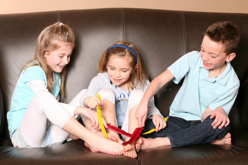 Kinder, die Füße mit Feder tickling sind stockbilder