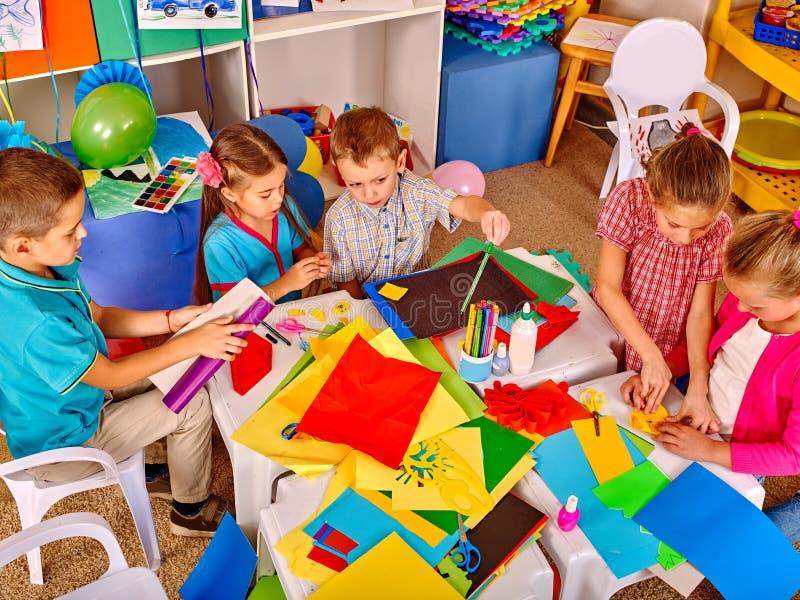 Kinder, die farbiges Papier auf Tabelle im Kindergarten halten lizenzfreie stockbilder