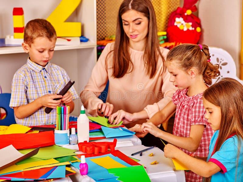 Kinder, die farbiges Papier auf Tabelle im Kindergarten halten lizenzfreies stockfoto