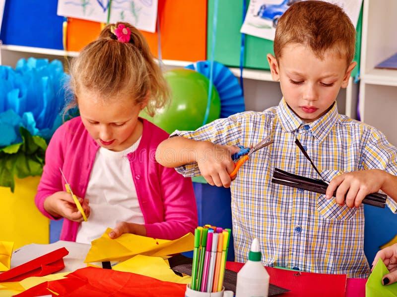 Kinder, die farbiges Papier auf Tabelle im Kindergarten halten lizenzfreies stockbild