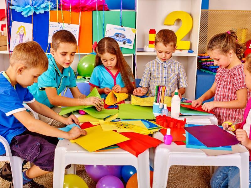 Kinder, die farbiges Papier auf Tabelle im Kindergarten halten stockfotos