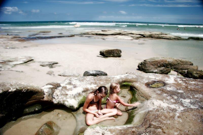 Kinder, die am Felsenpool spielen lizenzfreie stockfotos