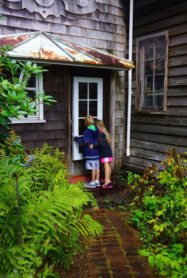 Kinder, die in Fenster spähen lizenzfreie stockfotografie