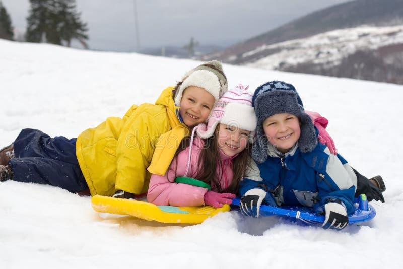 Kinder, die in frischen Schnee schieben lizenzfreies stockbild