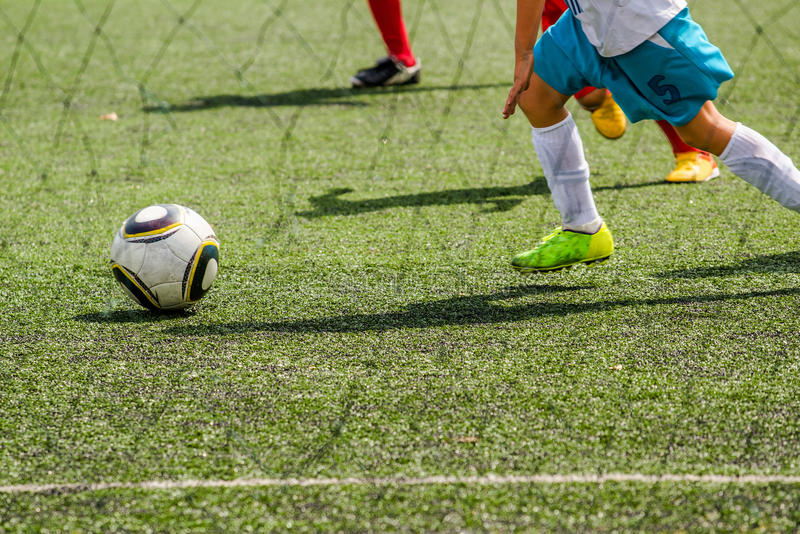 Kinder, die Fußball spielen stockfotografie