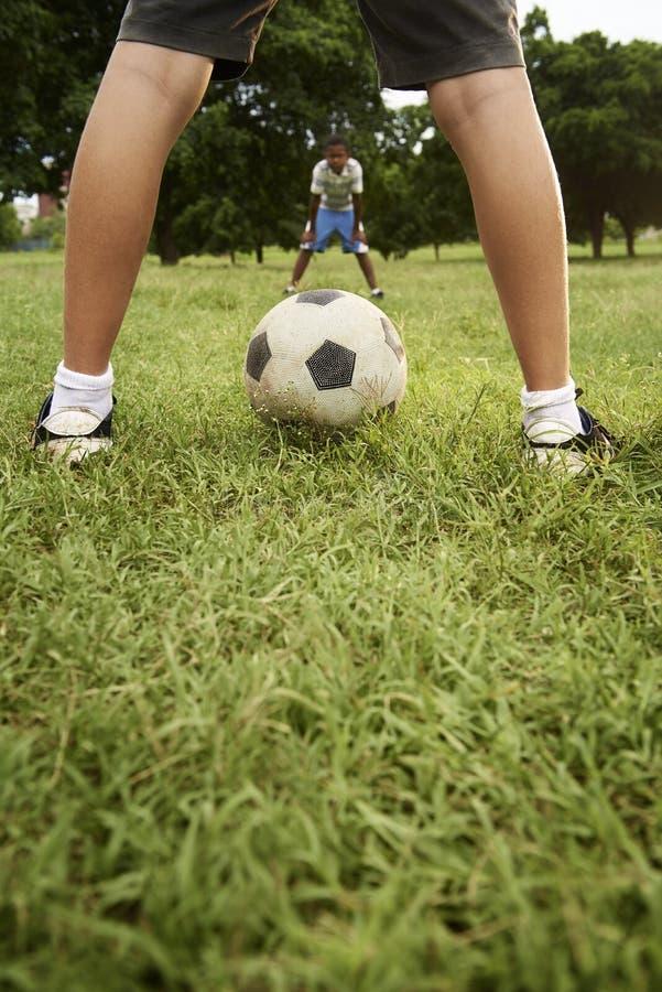 Kinder, die Fußball- und Fußballspiel im Park spielen stockfotos