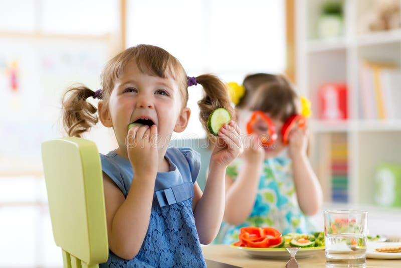 Kinder, die Gemüse im Kindergarten oder zu Hause essen lizenzfreie stockfotografie
