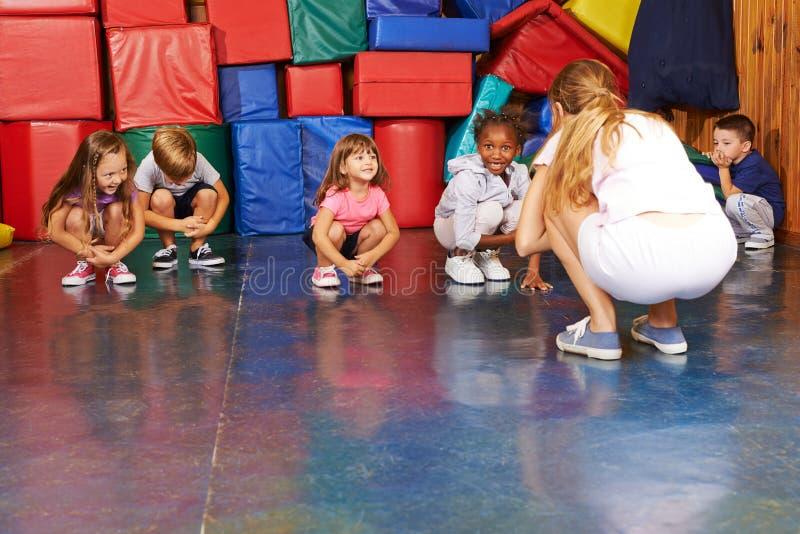 Kinder, die Gymnastik in der Leibeserziehung tun stockfotografie