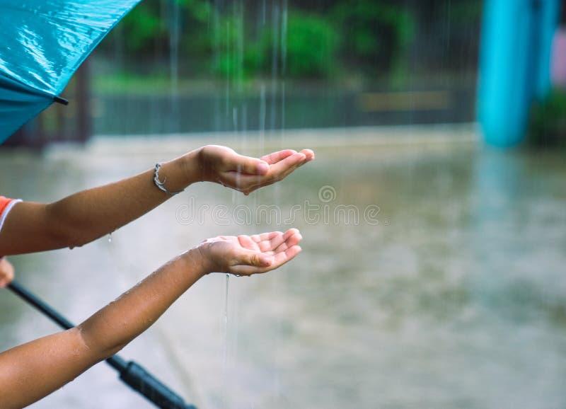 Kinder, die Hände in die anziehenden Tropfen des Regens des Regens einsetzen stockbild