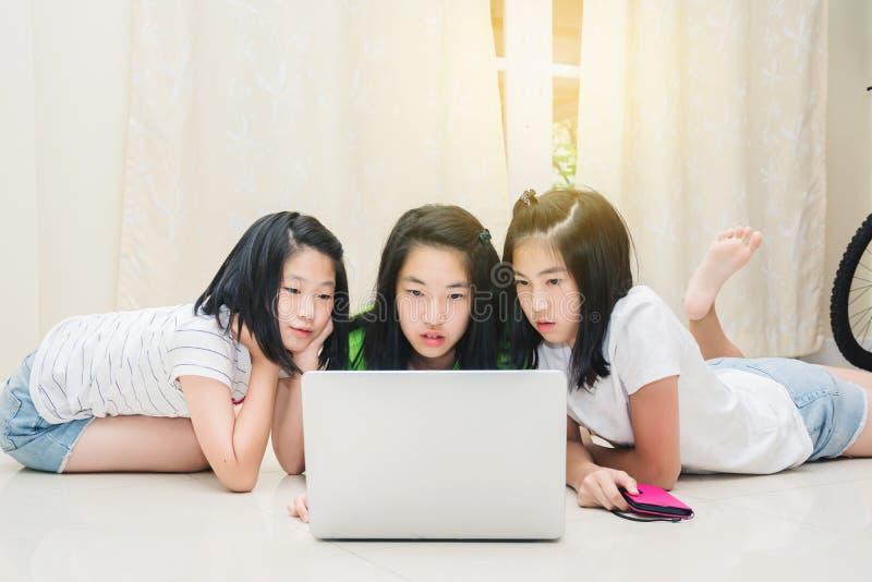 Kinder, die Hausarbeit zusammen mit Laptop tun stockbild