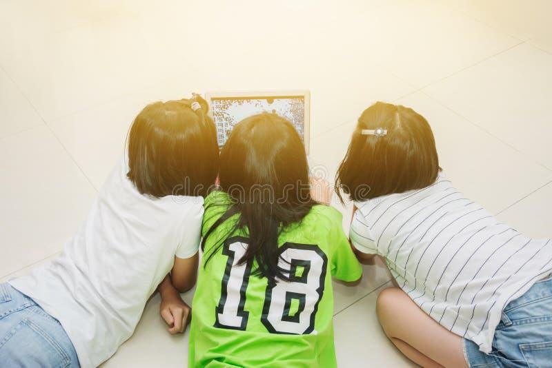 Kinder, die Hausarbeit zusammen mit Laptop tun lizenzfreie stockfotos