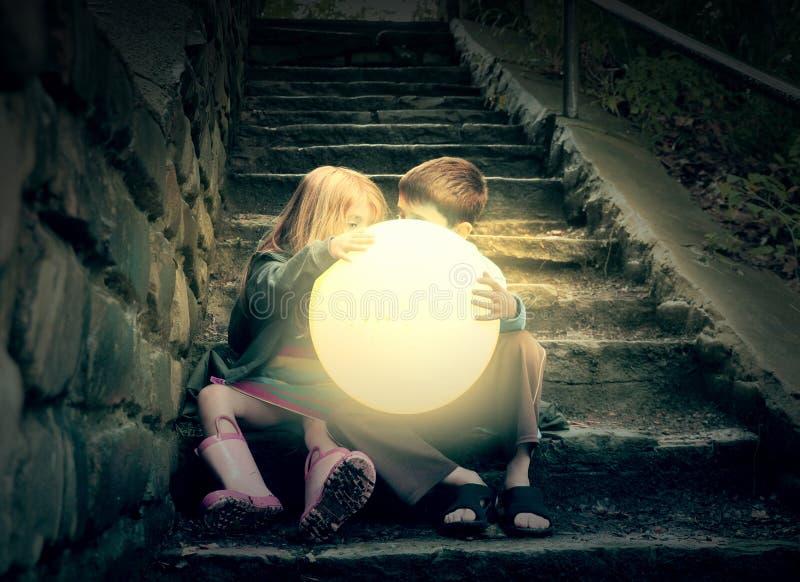 Kinder, die hellen Sonnenschein auf Treppe halten stockfotos