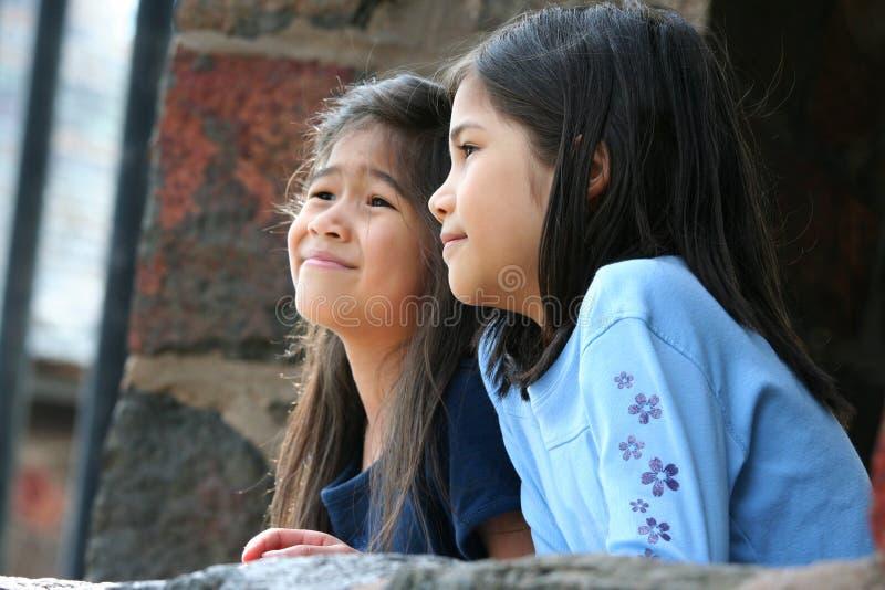 Kinder, die heraus über Steinwand schauen lizenzfreie stockfotografie