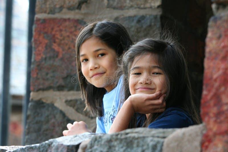 Kinder, die heraus über Steinwand schauen lizenzfreie stockfotos