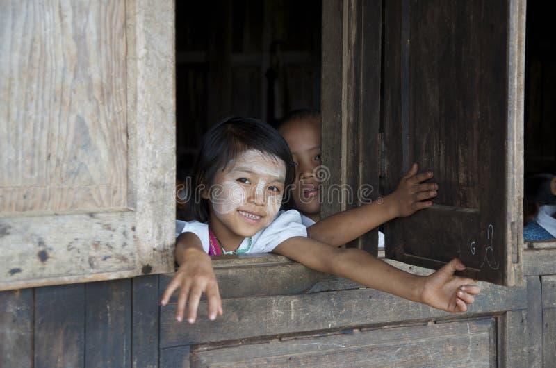 Kinder, die heraus das Fenster der Schule schauen stockfoto