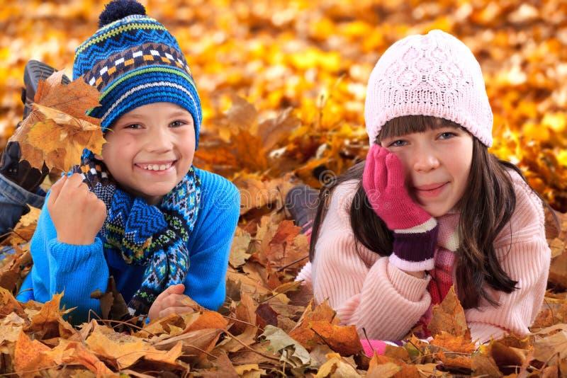 Kinder, die in Herbstblätter legen lizenzfreie stockfotos