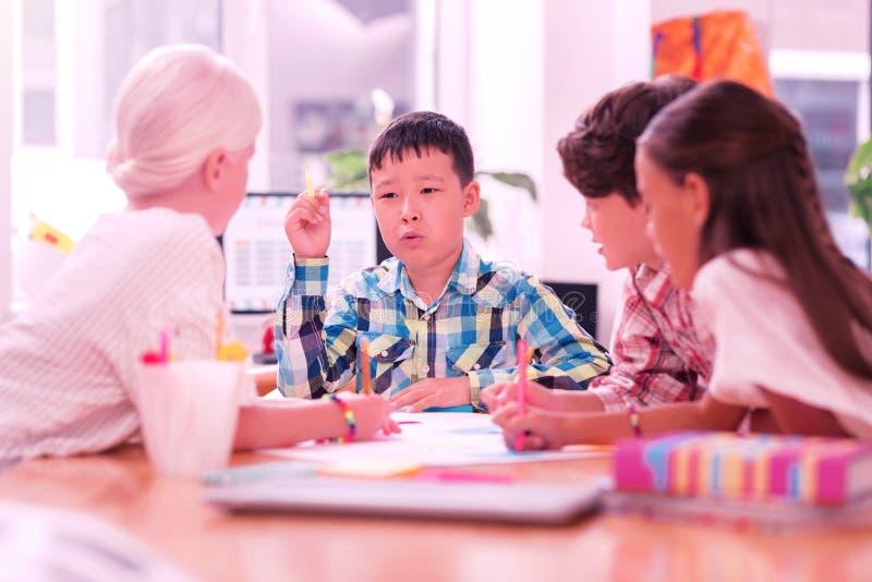 Kinder, die ihr Schulprojekt beim Zeichnen besprechen stockfotografie