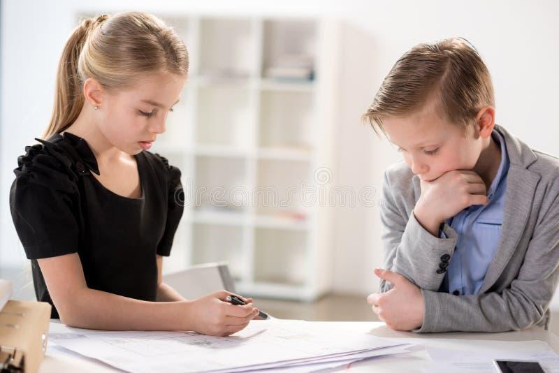 Kinder, die im Büro arbeiten stockfotos