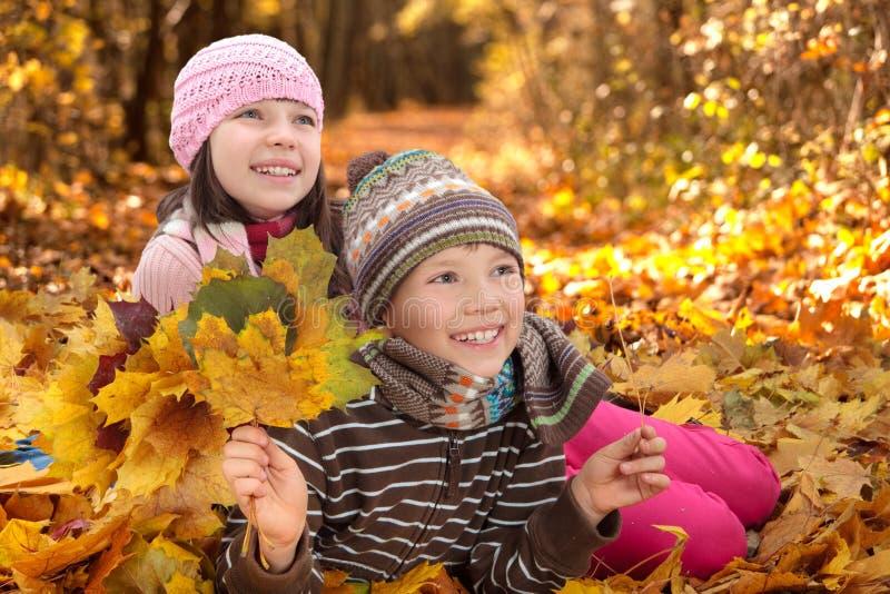Kinder, die im Herbst spielen stockfotos