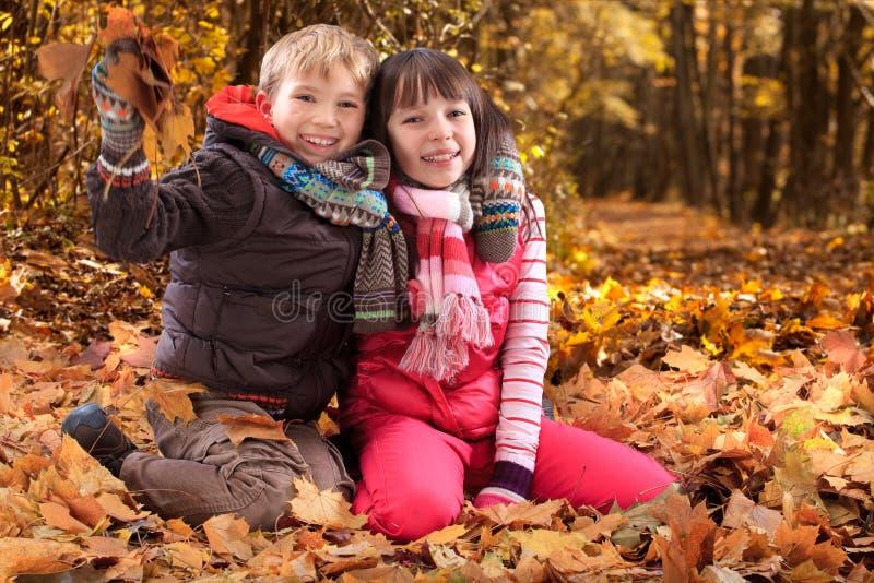 Kinder, die im Herbst spielen lizenzfreie stockbilder